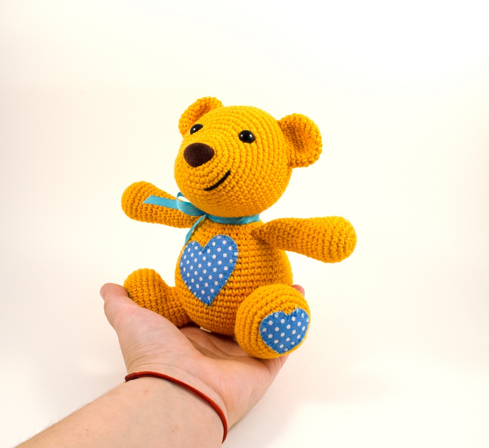 holding in hand crochet teddy bear toy