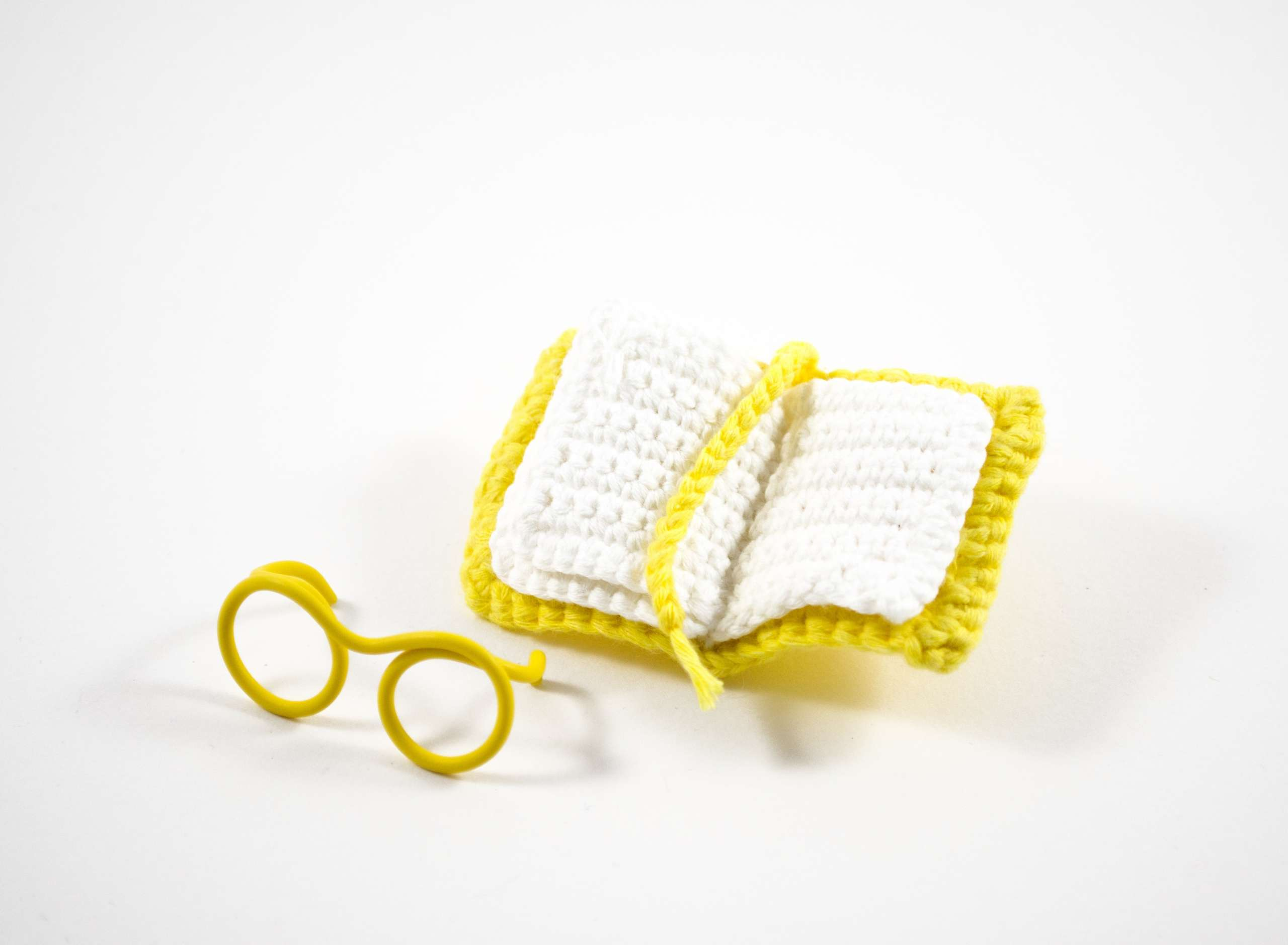 crochet book and wired glasses